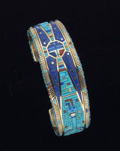 A Navajo bracelet: Raymond Yazzie. Comprising a 14 karat gold cuff band, narrowing slightly at each end, inset with over 650 individually cut and polished inlays of coral, turquoise and lapis lazuli, worked to depict a traditional Navajo Yei figure, standing with prayer feathers hung from his arms, placed on a mosaic background that tapers towards a central mask resembling a Hopi Sun kachina, complemented by a carved lightning bolt, raincloud motif, and horned globe, the top perimeter with a…