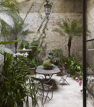courtyard with lovely wrought iron table and cafe chairs and wonderfully lush foliage
