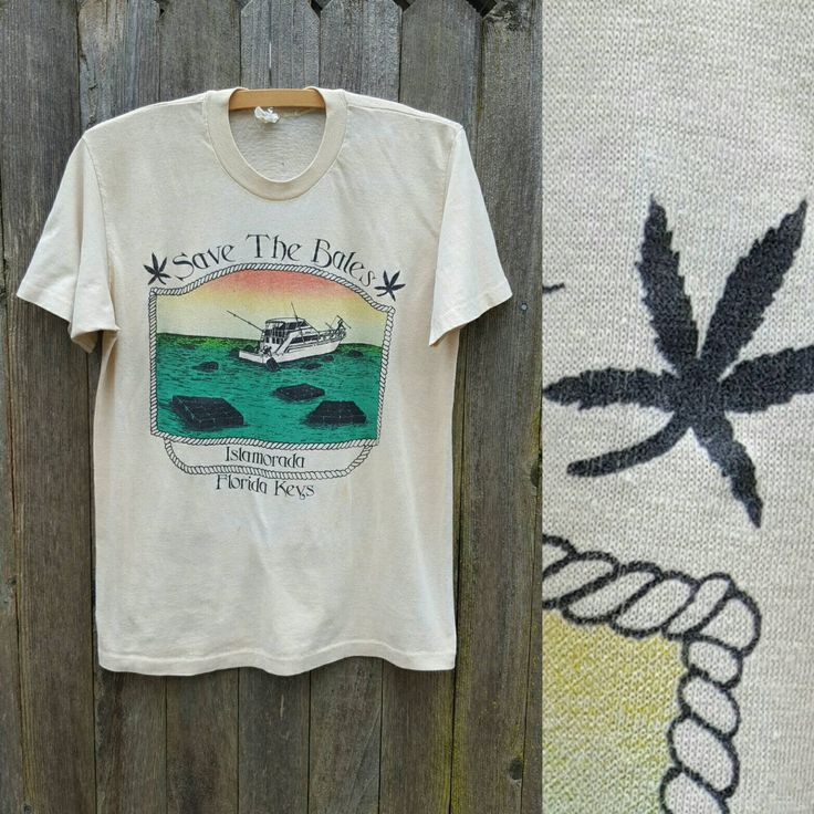 Vintage cannabis novelty tee. Tan tee has Florida Keys screen print on front featuring a small boat fishing bales out of the water; blank on back. Save the Bales is a spin on the Save the Whales slogan (dont see why there shouldnt be room in our hearts to save both); the bales, also known as square groupers, were typically thrown overboard or dropped from planes as a way to import cannabis into South Florida in the 1970s and 1980s. Tee is distressed to perfection -- soft, thin, and…