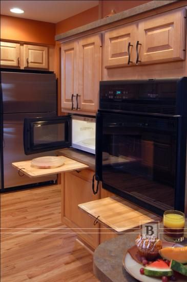 Here, pullout cutting boards provide a safe landing place out of the microwave and oven.