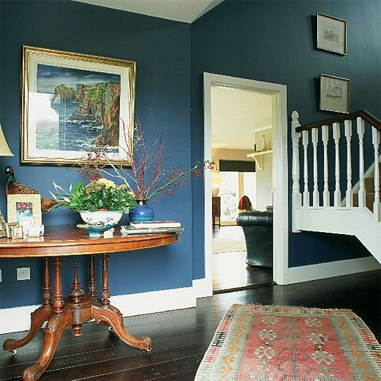 Hallway with blue walls, antique table and rug | Paint ...