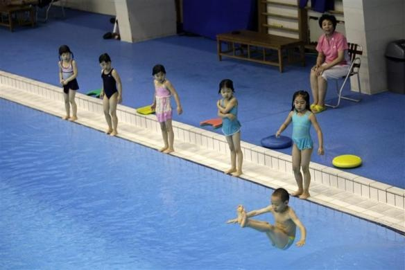Children practice jumping into a pool during a diving training session at a training center in Beijing July 27, 2011.  REUTERS/Jason Lee