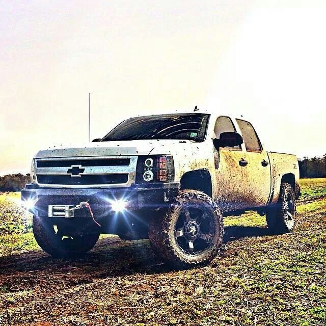 lifted white Chevrolet Silverado Hate the rims, interested in the bumper and headlights