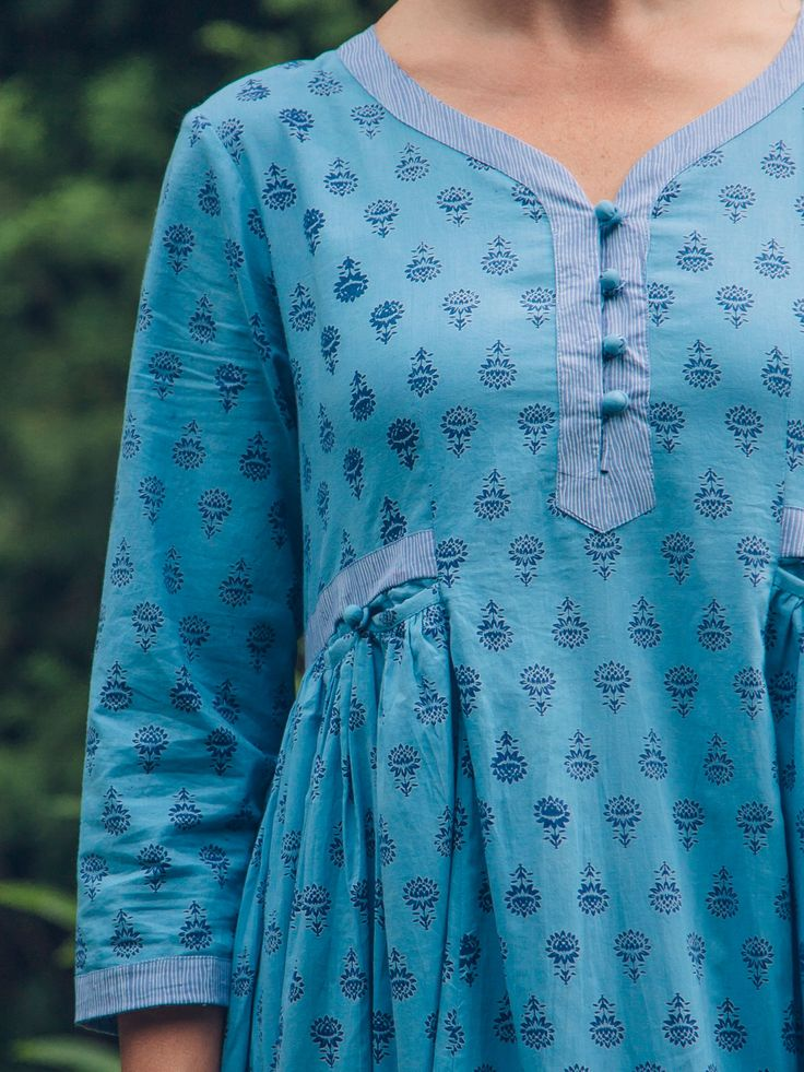 Gentle, baby blue ground comforts the soul and delivers such peaceful energy wherever it goes. The Leilani dress is artfully styled with a sweetheart neckline and tenderly trimmed with striped piping details on the hemline and on the collars edge. Teeny tiny gathers below the waist allow for an easy, flattering flow.