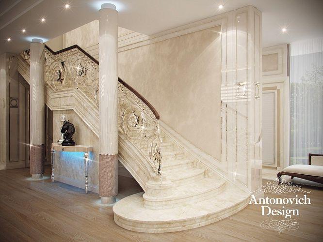 Дизайн холла и лестницы. Стильные капители колонн подсвечены современной подсветкой.  Прохладу белоснежного мрамора прекрасно компенсирует теплота полов из натурального дерева ценных пород.