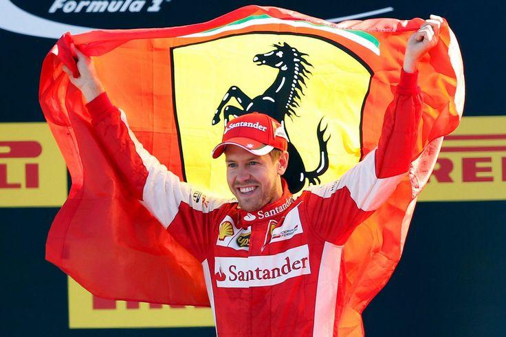 Ferrari's driver Sebastian Vettel holds a Ferrari flag as he celebrates his second place