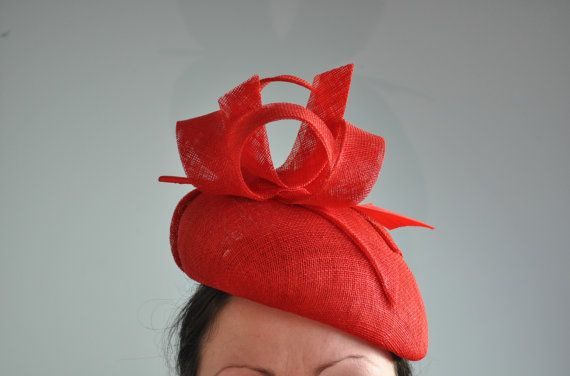 This charming headpiece is a beret style headpiece made from red sinamay and is adorned with matching sinamay loops and a red arrow feather