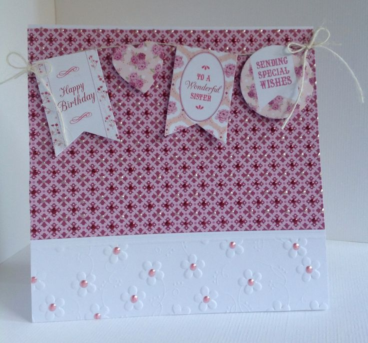 Card designed by Julie Hickey using Bonbon 6x6 paper pad, die cuts and template onto an embossed floral edge card blank. Gorgeous Pink girly card with lovely bunting sentiments and hearts on twine.