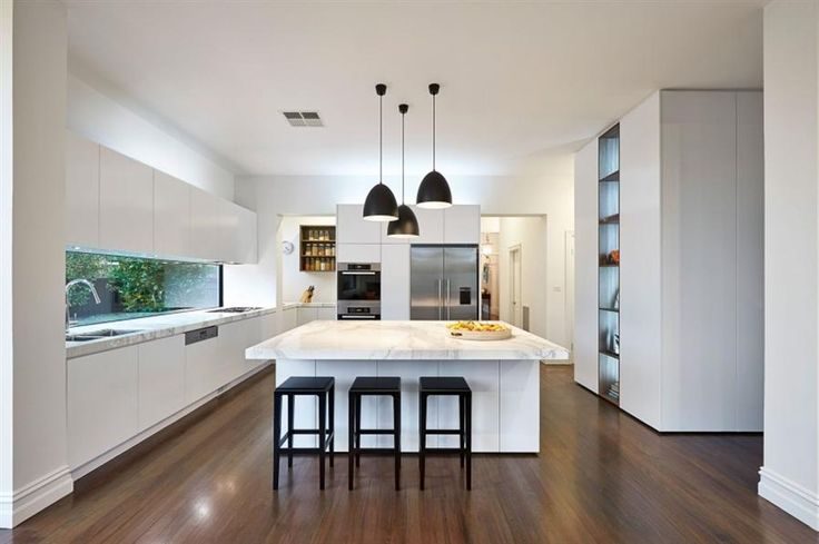 elegant kitchen design featuring white cabinetry with marble countertop, completed with large square island bench which illuminated by three black pendant lights