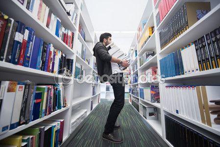 Студент, холдинг много книг в школьной библиотеке — стоковое изображение…