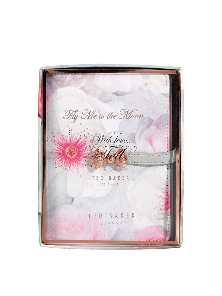 Keep all your travel essentials in one place with this stylish Travel Document Holder from Ted Baker. The statement Chelsea Border patterned cover features the words 'Fly Me To The Moon' in rose gold lettering, and the pink, faux-leather interior includes space for your passport, documents, travel tickets and a plastic ID window to fill with contact information. Documents are kept safe and secure with the bow shaped popper closure, and completing the travel accessory is a rose gold pe...