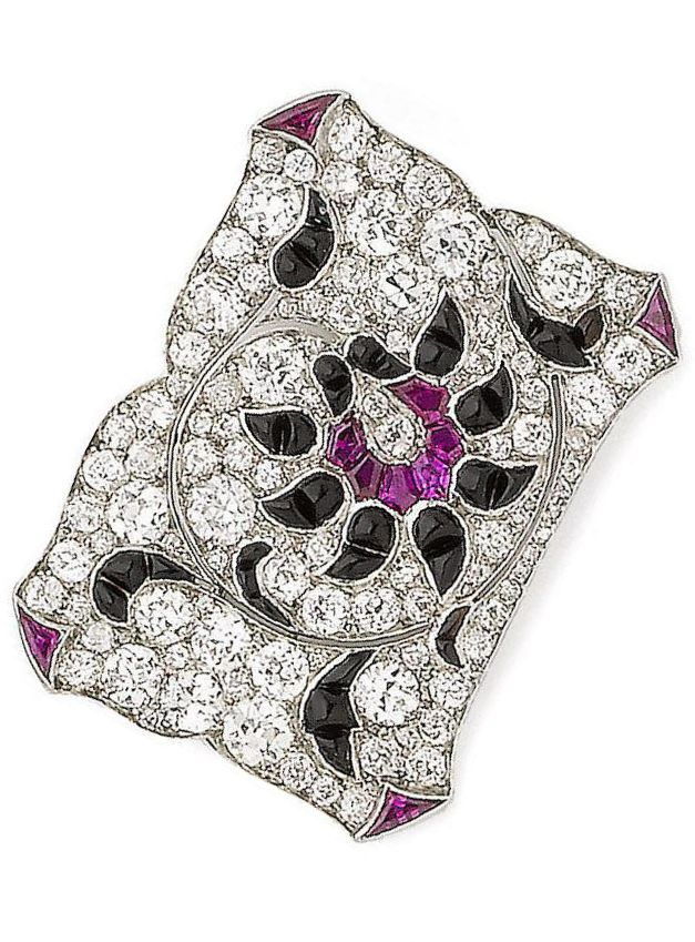 An Art Deco onyx, ruby, synthetic ruby and diamond brooch, circa 1925. The cushion-shaped and old brilliant-cut diamond plaque, decorated with a stylised calibré-cut rubies, synthetic rubies and onyx flower, diamonds, later pin fitting. #ArtDeco #vintage #brooch