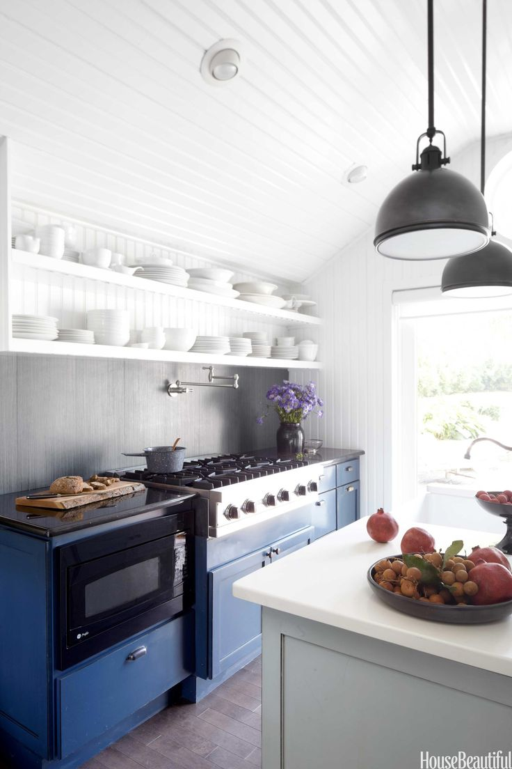 A 48-inch six-burner Viking cooktop and a GE Profile microwave are set into old-fashioned navy blue cabinets, made by Fieldstone Cabinetry, and topped with Absolute Black granite. Danze pot filler. Marion pendants in Old Bronze by Hudson Valley Lighting have a vintage look. The dishes are a mix of new and old.   - HouseBeautiful.com