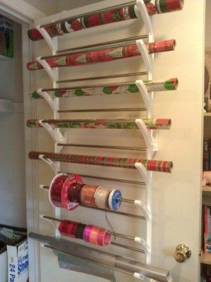 Over-door shoe rack re-purposed as a wrapping paper/ribbon organizer - could fold tissue paper over the fixed rods in back AND could also use this for tablecloths and or extra sheet storage to free up space in linen closet (beach towels, etc)