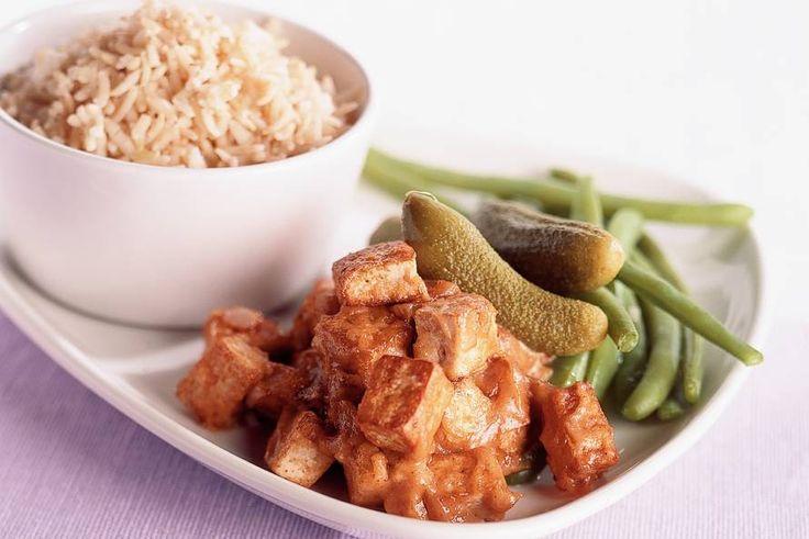 Volkoren rijst met tofu in pindasaus, geserveerd  met sperziebonen
