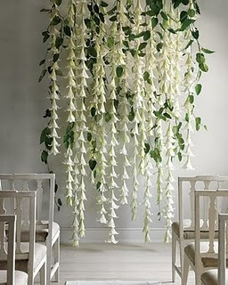 String together long garlands of silk flowers and mix some leaved through the display to create a beautiful backdrop.