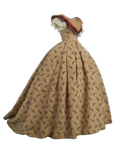 Vestido formado por cuerpo y falda en gros de Nápoles con decoración estampada en color burdeos. El cuerpo, armado con ballenas, lleva escote en pico adornado con un tableado en organza de seda, cinta de raso y volante de encaje. La falda es larga, con vuelo y una estrecha cinturilla.