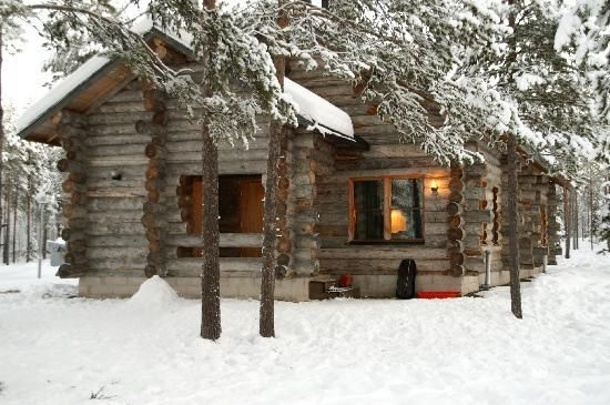 Mountain cabin in the snow welcoming lights inside