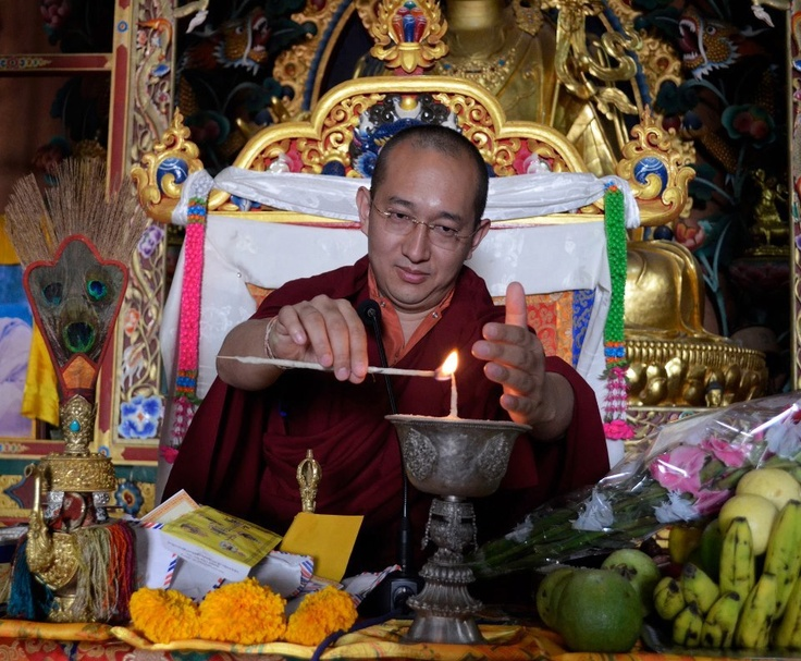 Venerable Khangser Rinpoche lighting a lamp.
