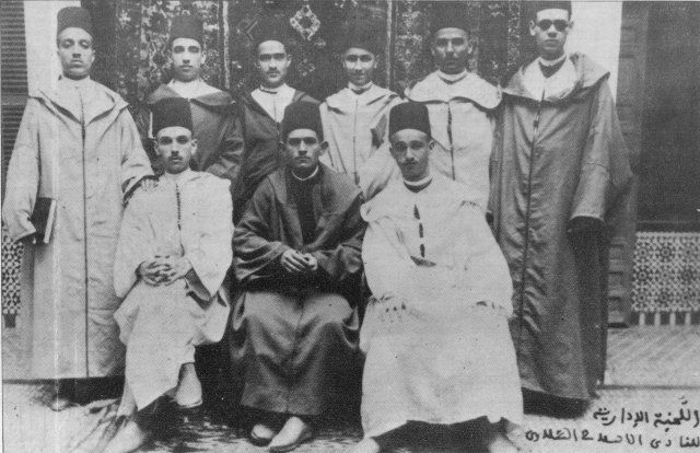 Les membres du Conseil d'Administration du Club Littéraire de Salé On reconnait debout de gauche à droite: Abderrahman Aouad, Mekki Aouad, Abdelkrim Bouâllou, qui sera appelé à succéder à l'actuel président, Mohammed Zemzami Jaïdi, Ahmed Hassar, Mohammed Chemao. Assis au milieu de la photo: le président en exercice du Club Abou Bakr Sbihi, avec à sa droite Driss Aouad et à sa gauche Omar Aouad - Photo prise en 1927.