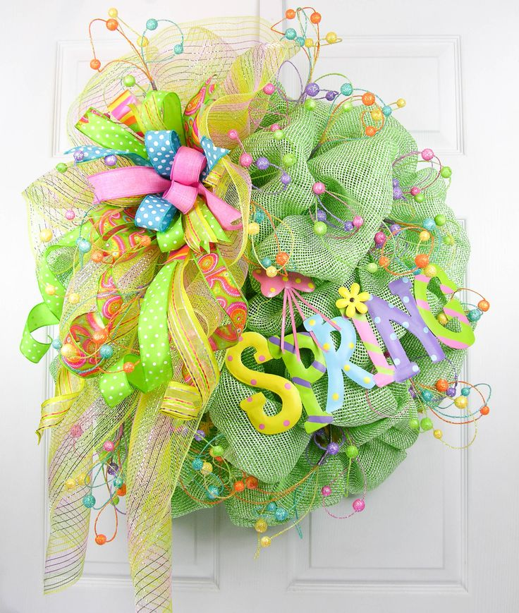 A premium deco mesh designer quality wreath with pastel colors of spring. The wreath is filled with twirly glitter stems, a large multi-patterned Terri Bow and a Spring metal sign with coordinating co