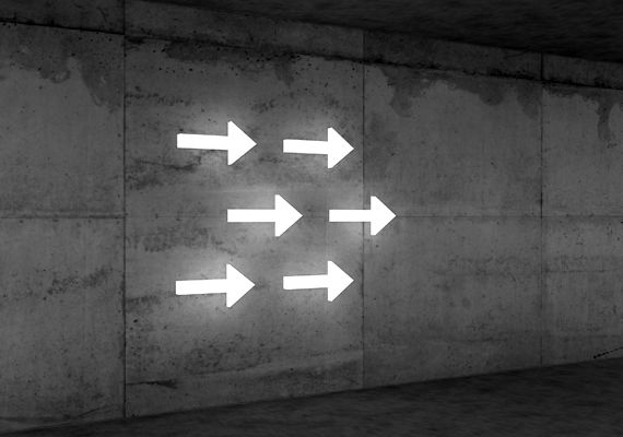Illuminated Arrows on Concrete Wall | Creative Wayfinding and Signage Design