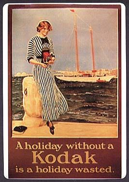 """Reproduction on metal of c. 1920s poster, """"A holiday without a Kodak is a holiday wasted."""""""