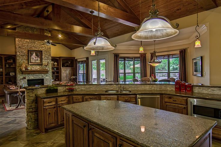 The significantly sized granite island is practical and pretty as the center piece of the - Knotty hickory kitchen cabinets ...
