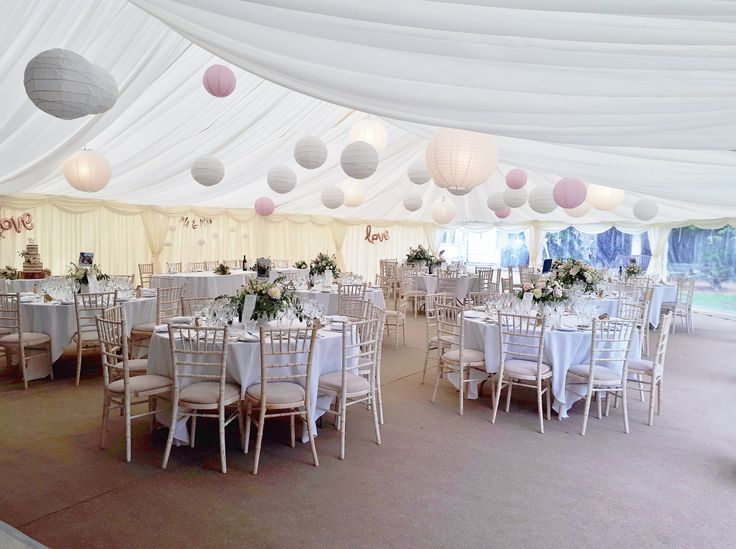 A beautiful wedding marquee in Titchfield, Hampshire with Paper lanterns and stunning flower displays in vintage china vases.