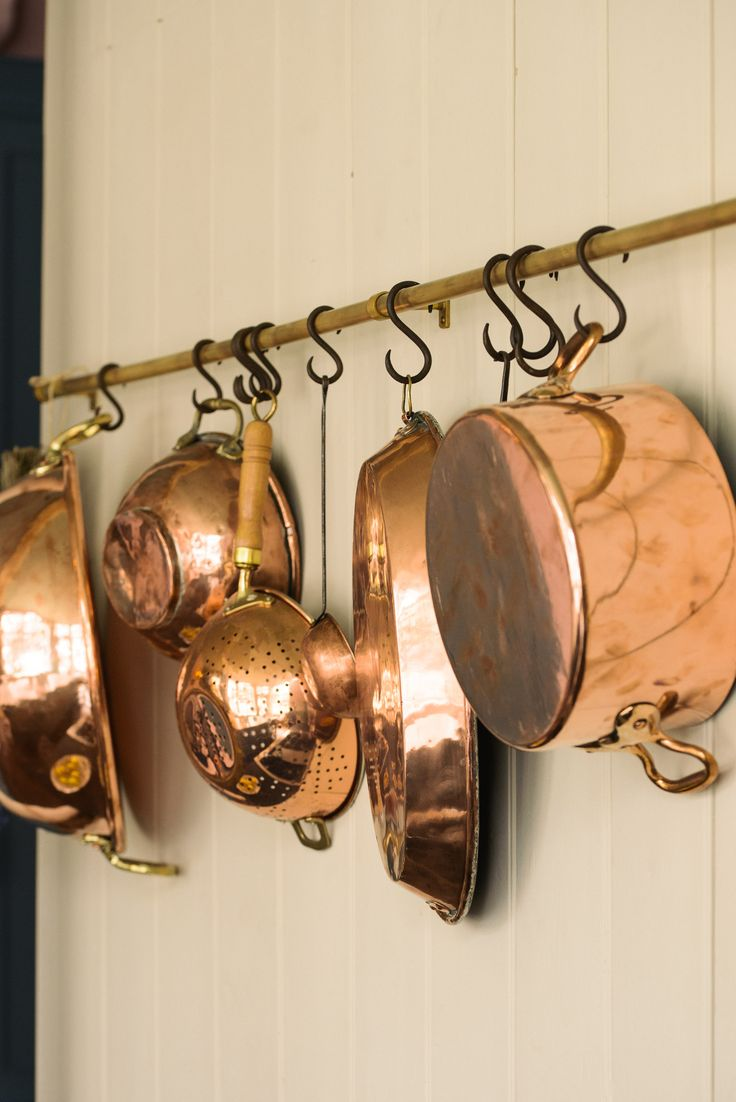 Lots of lovely old copper pans hanging from an aged brass rail