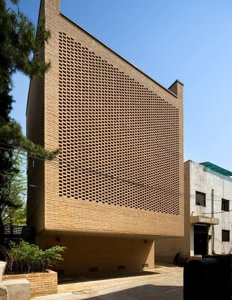 A towering wall of perforated brickwork lets light filter gently into the rooms of this house: