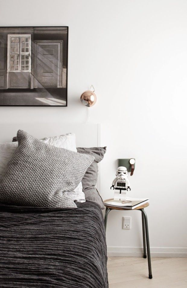 copper reading light stool as a bedside table and dark grey bedding in the bedroom of a beautifully captured danish johanne dueholm