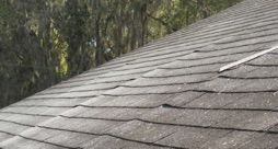 What causes shingles to buckle along a line on the roof?