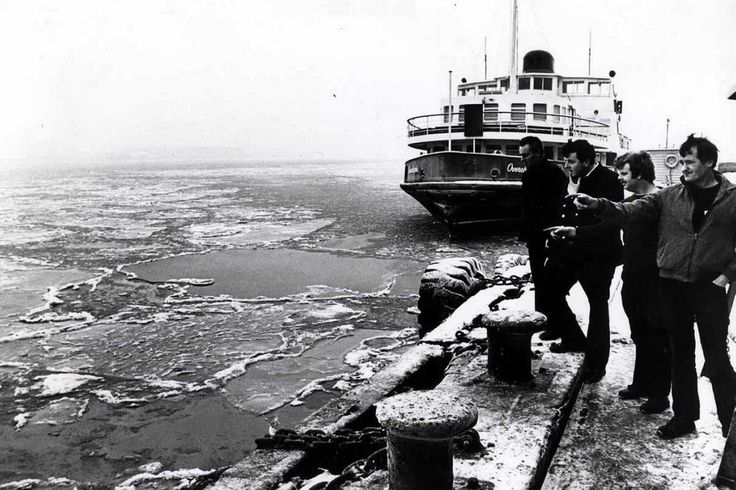 People look at the ice on the river Mersey with the Seacombe ferry in the background