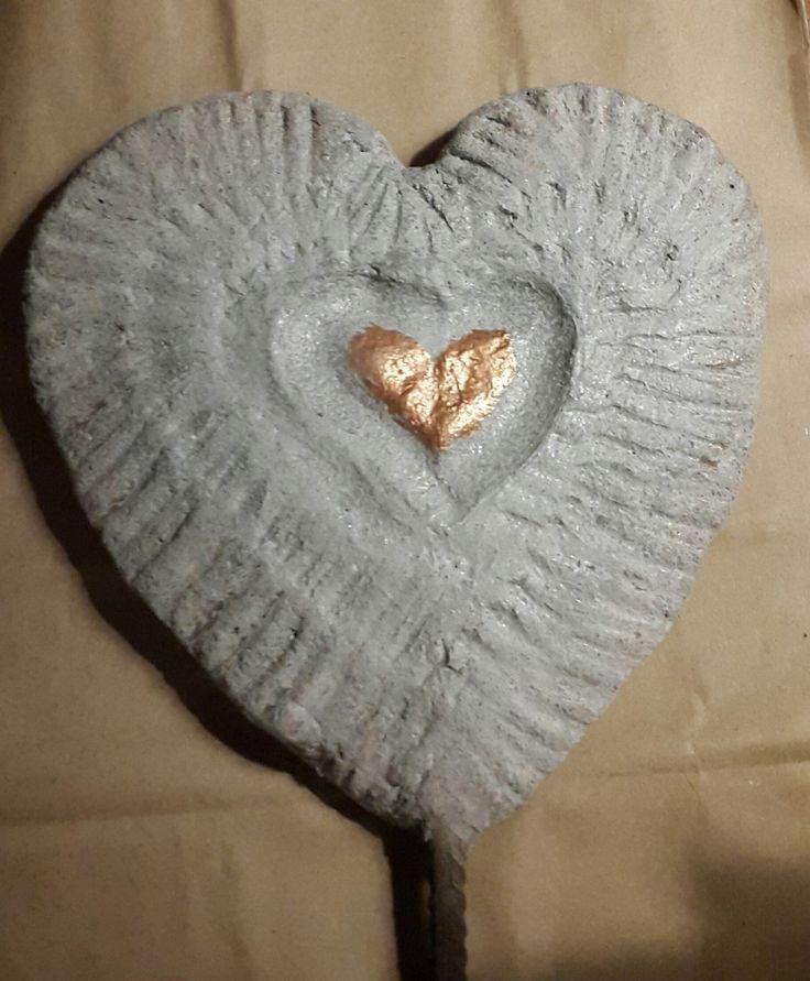Hjärta gjort i betong på ett armeringsjärn för att ha i trädgården