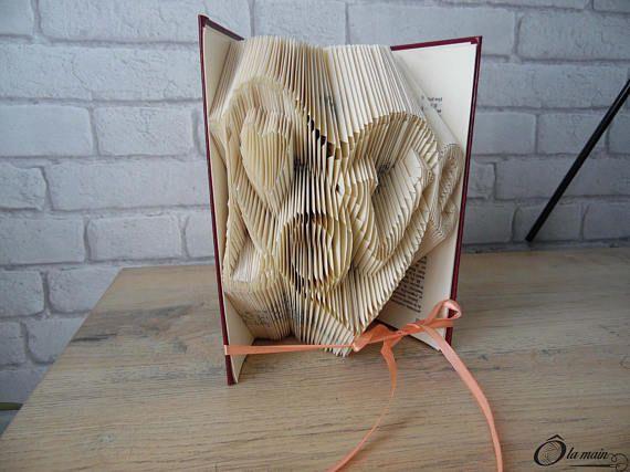 La collection A Livre Ouvert est une série de livres doccasion transformés en objets de décoration via plusieurs techniques (découpage, pliage ou décou-pliage). Chaque page est découpée et/ou pliée à la main pour donner vie à un motif.  Le modèle De tout mon coeur est un livre plié pour représenter 2 coeurs et le mot Love. VENDU SEUL