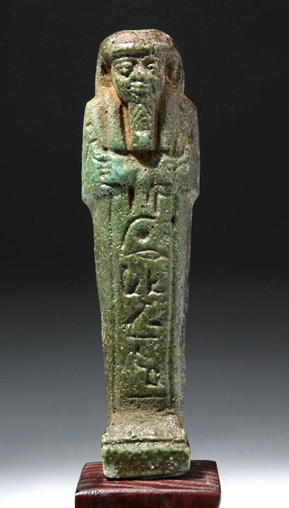 "Egypt, Third Intermediate Period, Nubian Kingdom, 25th Dynasty, ca. 760 to 656 BCE. A dark turquoise green glazed faience ushabti, molded in mummiform posture with a smooth wig and beard. The figure holds a hoe and sickle in its crossed arms, ready to work in the afterlife. A band of hieroglyphic inscription runs down the front and onto the back. It reads: ""Illuminate the Osiris Ta-sheri-en-ta-ihet, called Ta-Psamtik, born to Pa-di-neith."";  ARTEMIS GALLERY 3/15/2017"