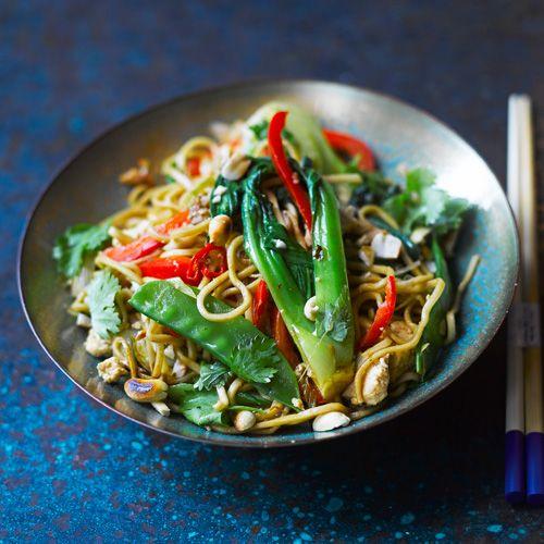 Een heerlijk kleurrijk roerbakgerecht met rijstnoedels, verse groente en tofu. Ideaal voor als je een dagje geen vlees of vis wilt eten.    1 Kook de noedels en giet ze af. Rooster de pinda's in een droge pan goudbruin. Verhit de arachideolie in een...