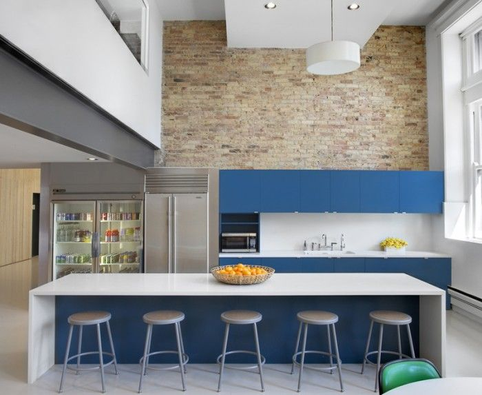 I like the simplicity of this kitchen. High table, high stools, storage cabinets, a big fridge and BIG fruit bowl! (RG)