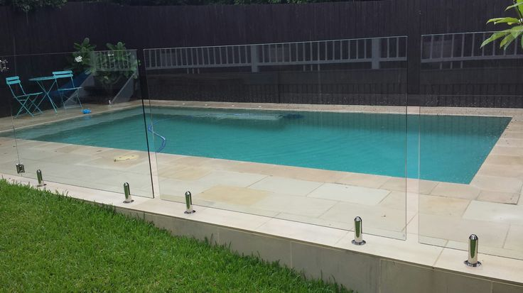 Sawn and sandblasted sandstone paving and coping around pool. Glass pool fence. EcoBuilt Landscaping Brisbane. Follow EcoBuilt Landscaping on Facebook.