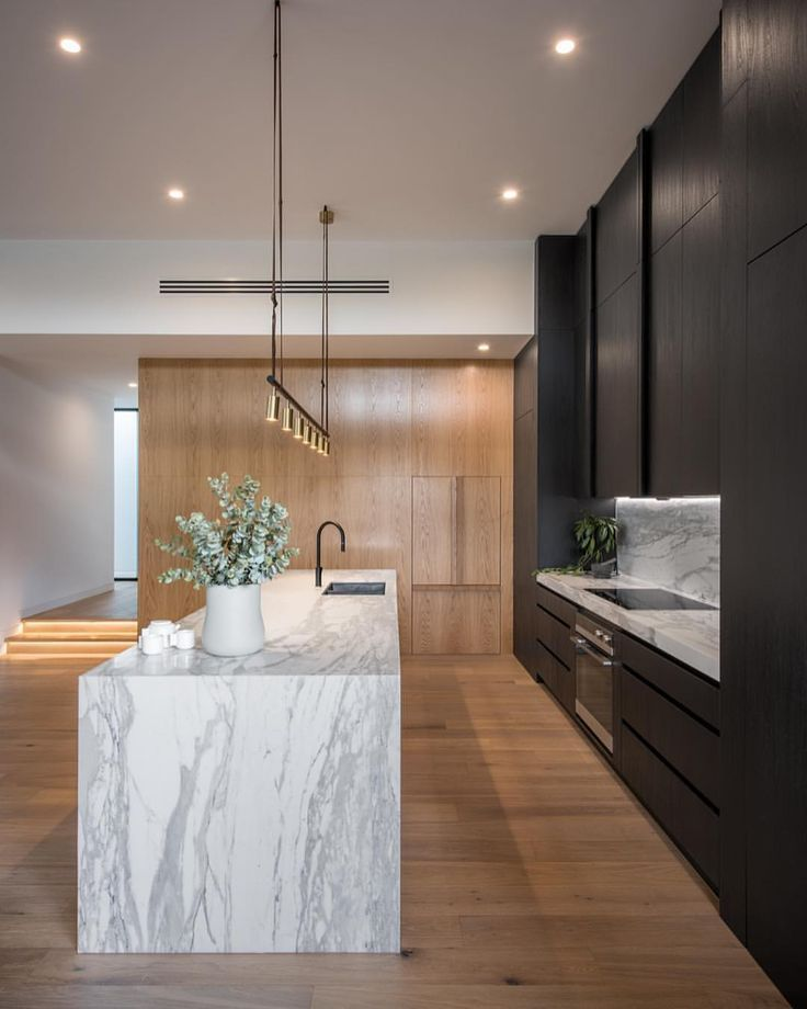 Contemporary design kitchen with black furniture, central island and marble worktop and suspensions above the island