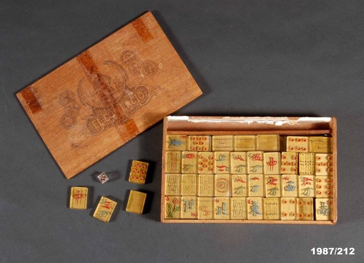 Mah jong set made in a Japanese prisoner of war camp. The tiles are made from the windscreen of a Japanese trainer aircraft. From the collection of the Air Force Museum of New Zealand.