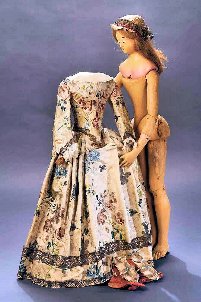 Georgian Wooden Doll & Gown, 1700's, Northern Italy - Original jointed body with well-shaped elongated legs - Hands restored - Human hair wig, Woven-silk gown with homespun lining, Bone-shaped bodice with back lacing closure, Sleeves with silk tie ribbons & Gilt metallic borders - Original Chemise, Petticoat, Hand-woven stockings, Hand-stitched sandals with Gemstone accents and Silk (matching gown) Soles. Theriaults.com