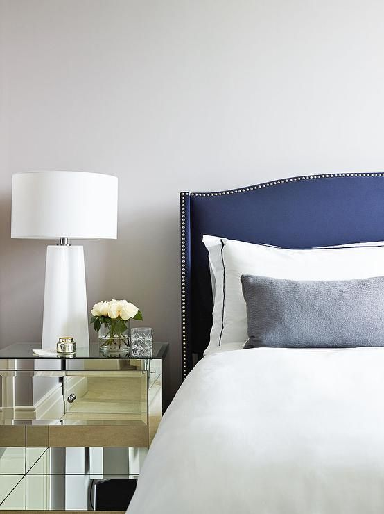 Chic bedroom features a curved navy nailhead headboard on bed dressed in white and navy bedding as ...
