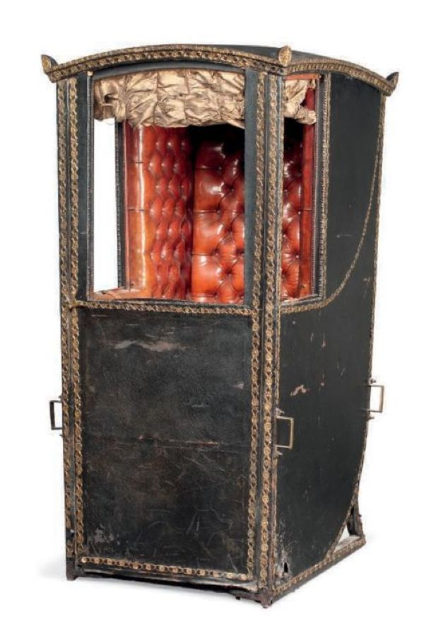 George III, late 18thC, Gilt and leather sedan chair. Hinged canopy above a hinged door enclosing a fitted red leather interior with button-back seat, bone fitted sliding compartmented glass windows and silk curtains, both sides with fitted brackets. Monogrammed 'EK' (no poles). Christies