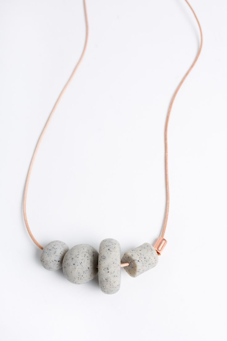 Beaded statement necklace with stone colored handmade beds and copper pipe. Features natural leather cord, lobster claw and hook closure. Origin: Made in Raleigh, NC Materials: Polymer clay beads; cop                                                                                                                                                                                 More