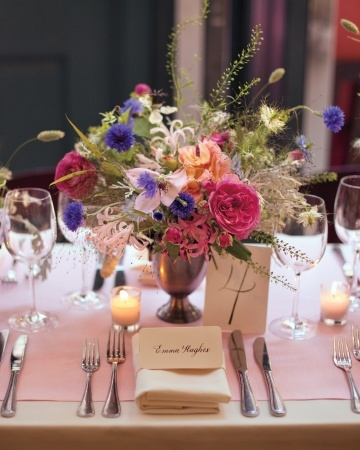 Brightly colored floral centerpiece and flickering votice candles set a romantic scene