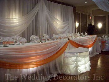 Like the orange band on tulle and the lighting for wedding party's table.
