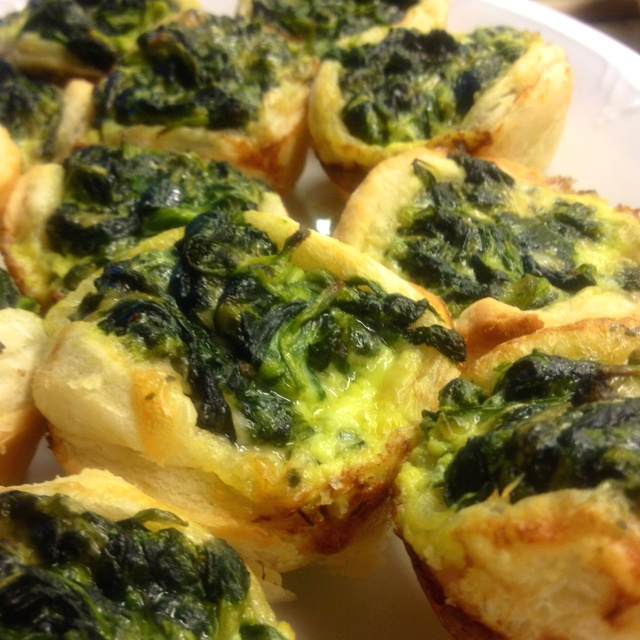 Individual puff pastry cases filled with spinach leaves ...
