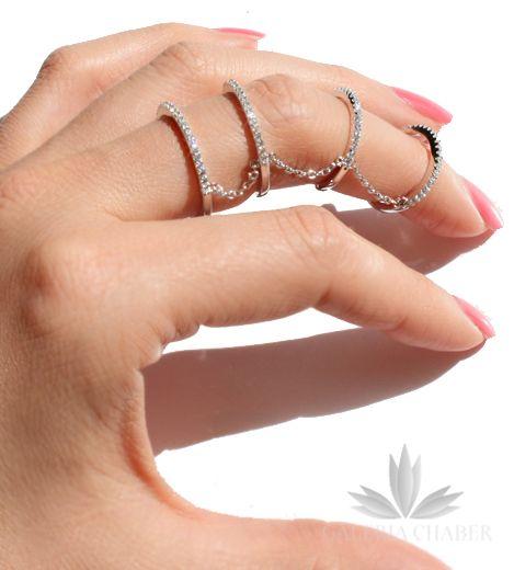 Multiring wykonany ze srebra próby 925, rodowany. Pierścionek wysadzany cyrkoniami o szlifie brylantowym. Obrączki połączone są łańcuszkami, pierwsze dwie w rozmiarze 16, kolejne regulowane, tak, aby dopasować się do palca.
